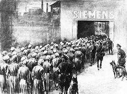 Dès les premiers camps de concentration, l'utilisation du travail forcé est au centre du système concentrationnaire et s'inscrit dans l'idéologie et le projet politique du national-socialisme. Cette politique connaît cependant un tournant au printemps 1942 avec l'intégration des camps dans une économie de guerre totale. La mobilisation de toutes les capacités de travail des internés vient au premier plan pour alimenter la machine de guerre nazie et le régime met l'accent sur la fonction de rentabilité des camps de concentration selon une méthode planifiée d'exécution lente. Des entreprises allemandes contrôlées par la SS ou privées, comme Siemens, bénéficiaient de l'utilisation à bas coût de cette main d'œuvre captive pour soutenir l'effort de guerre. Plusieurs usines Siemens ont employé des déportés, notamment dans des commandos de travail attenants aux camps de Sachsenhausen, d'Auschwitz, ou de Ravensbrück, le camp de concentration pour femmes qui est ici représenté. -
